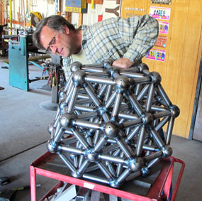 Artist Kevin Caron inspecting his large truncated octahedron