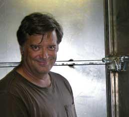 Sculptor Kevin Caron walks in his new door