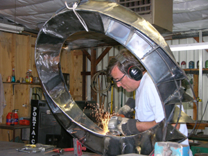 Sculptor Kevin Caron grinding a new free-standing fine art sculpture
