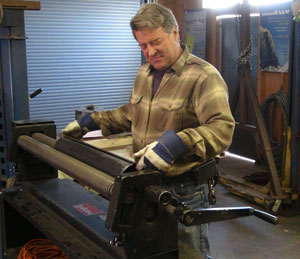 Artist Kevin Caron creating part of a sculpture on his slip roll.