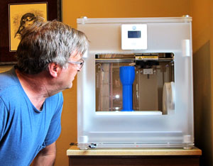 Artist Kevin Caron looking into his 3-D printer