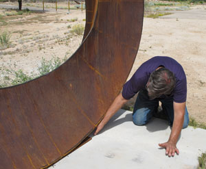 Artist Kevin Caron checking the base of his sculpture Wherever You Go, There You Are during installation